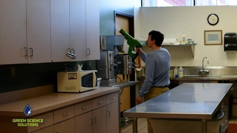 A man is spraying down the kitchen with SOA solution to sterilize the cabinets and countertops.