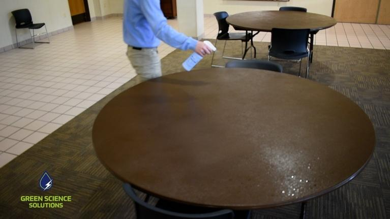 A man is cleaning a table using the SOA solution to sterilize its surface.